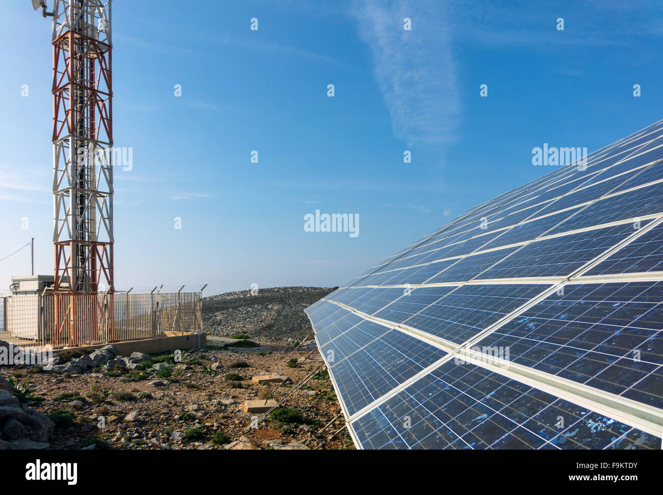 Solar panels and mobile phone mast against blue sky - Stock Image