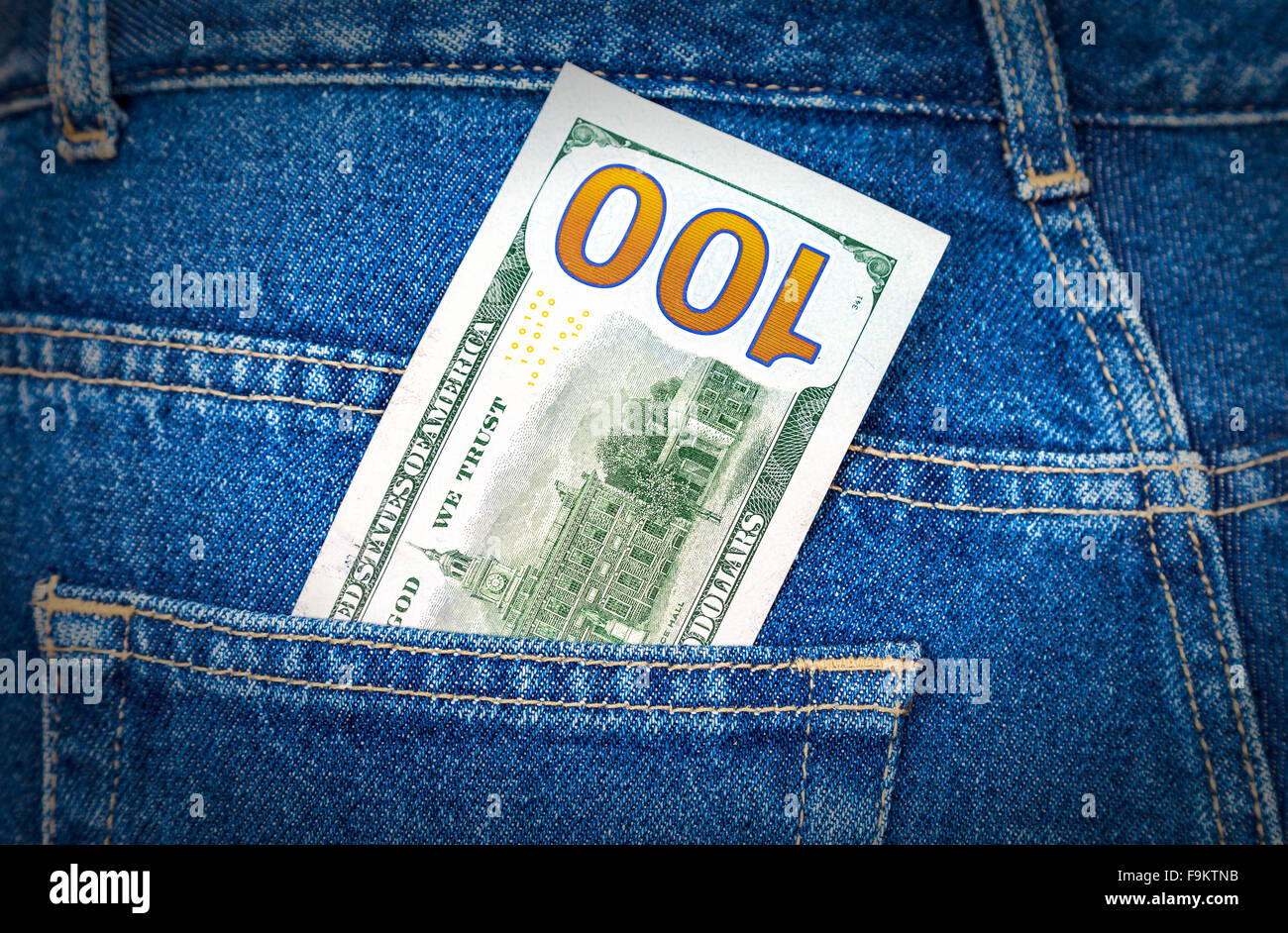 One hundred dollars bill sticking out of the back jeans pocket - Stock Image