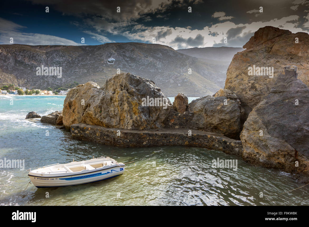 Small white rowing boat in small harbour harbor, Kalymnos, Greece - Stock Image