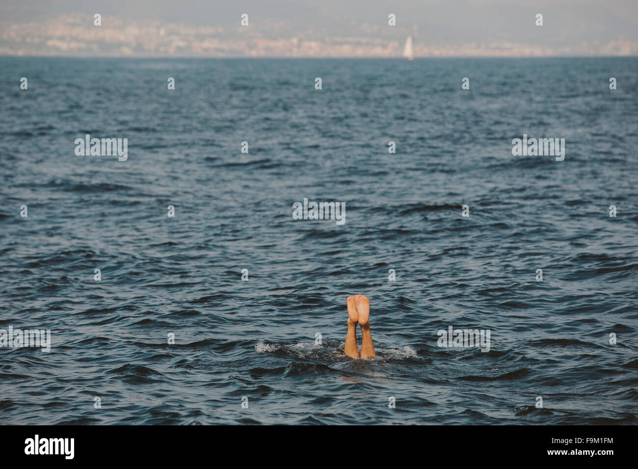 Feet of a man having a bath in front of Barcelona, Spain - Stock Image