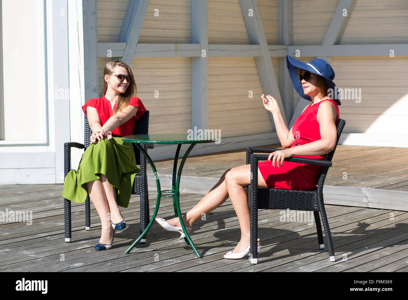 Small-talk between two aristocratic ladies in terrace - Stock Image