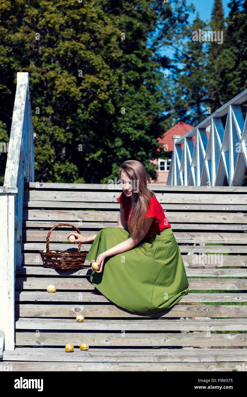 Girl in long skirt collects dropped apples - Stock Image