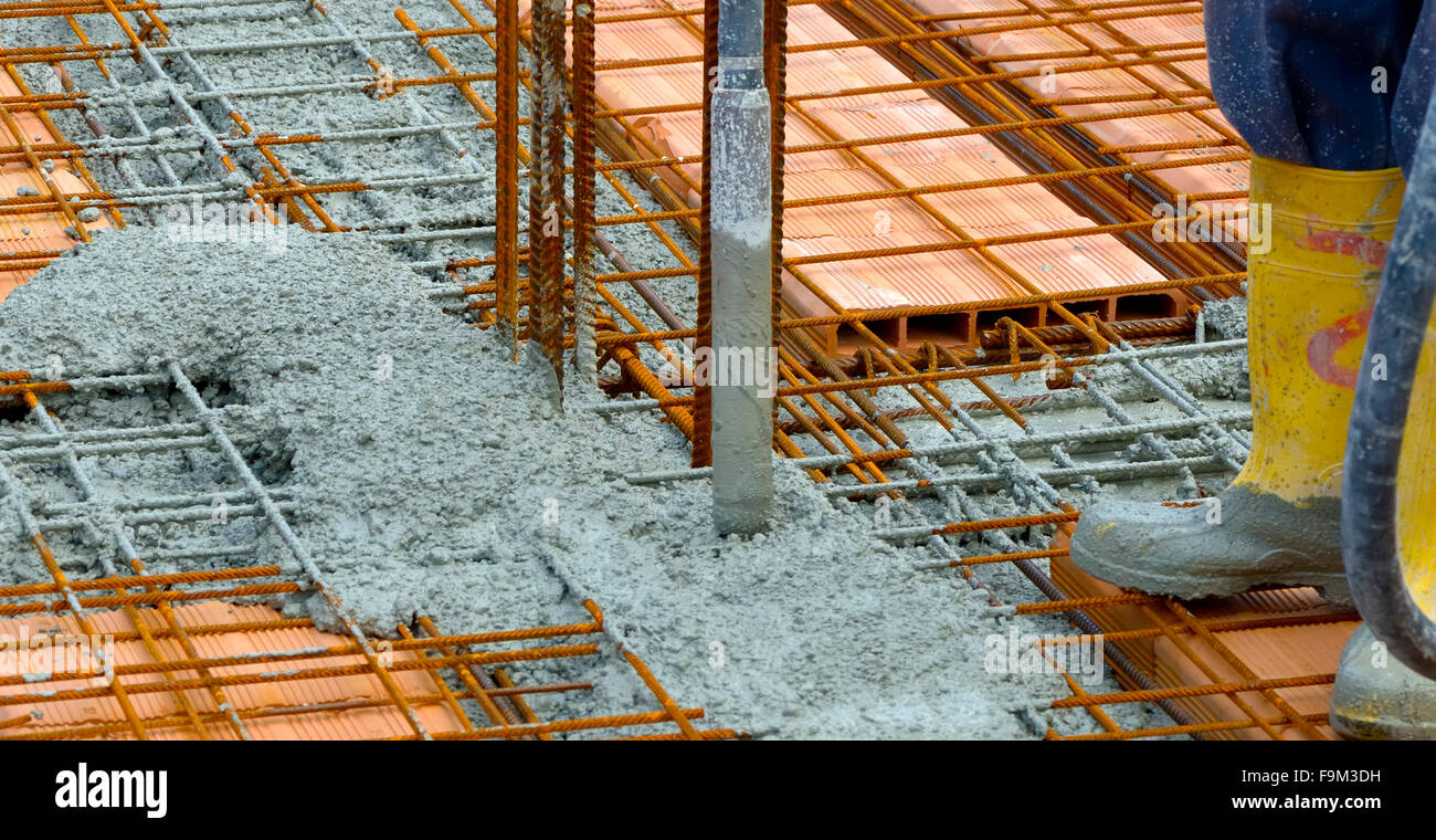Construction worker compacting liquid cement in reinforcement form work during concreting floors pouring works Stock Photo