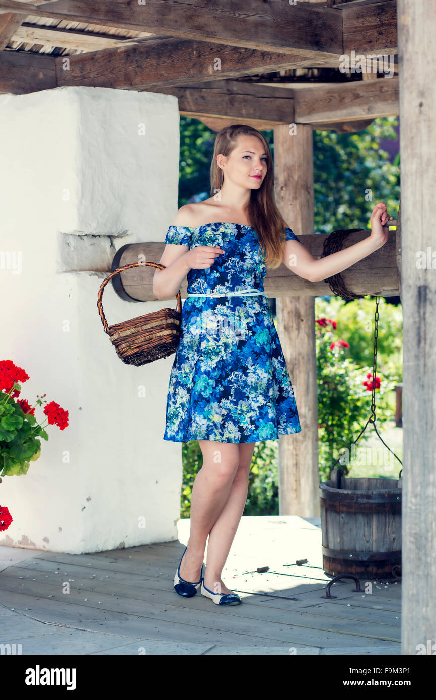 Adorable lady standing on the old well Stock Photo