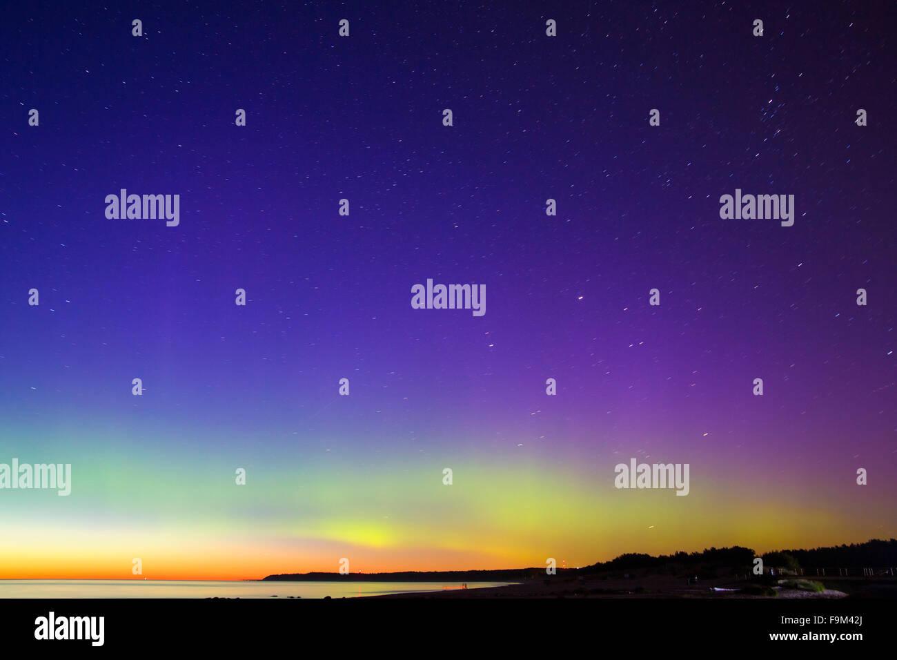 Warm Aurora Borealis above the Northern Sea - Stock Image