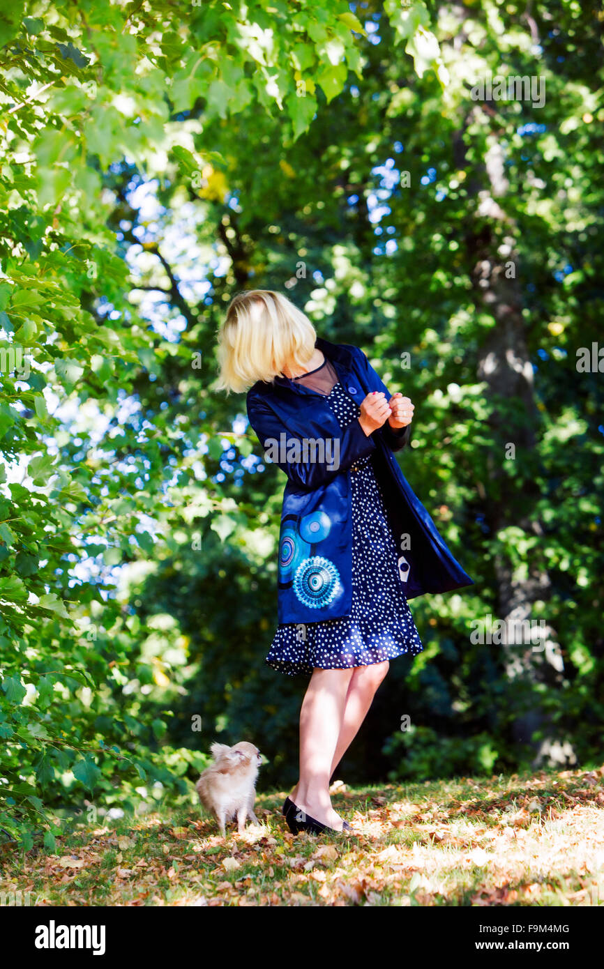Woman playing hide and seek with dog - Stock Image