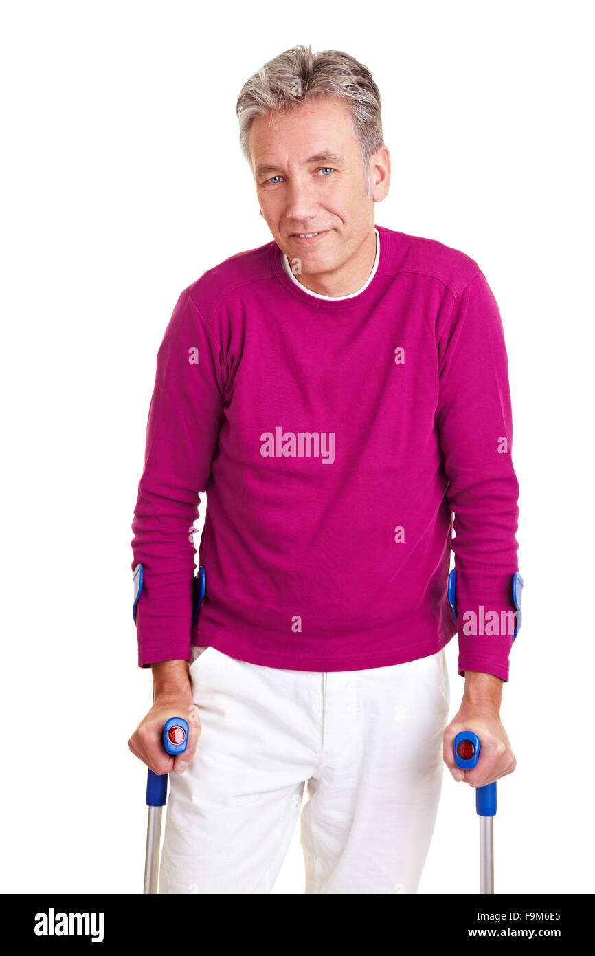 Smiling senior man walking with two crutches - Stock Image