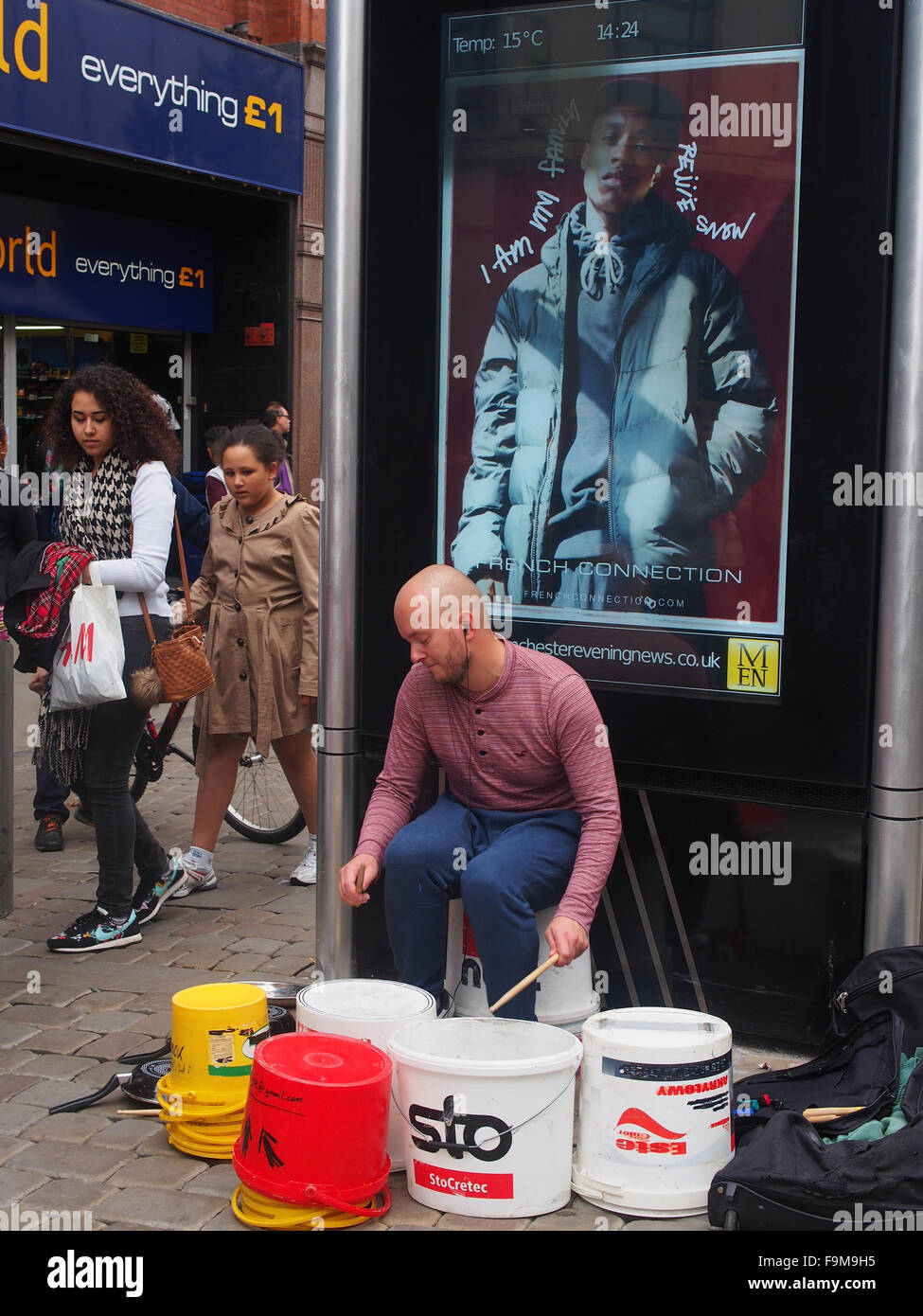 Man playing improvised drums (paint containers), one of the many street performers in Manchester city centre, UK. - Stock Image