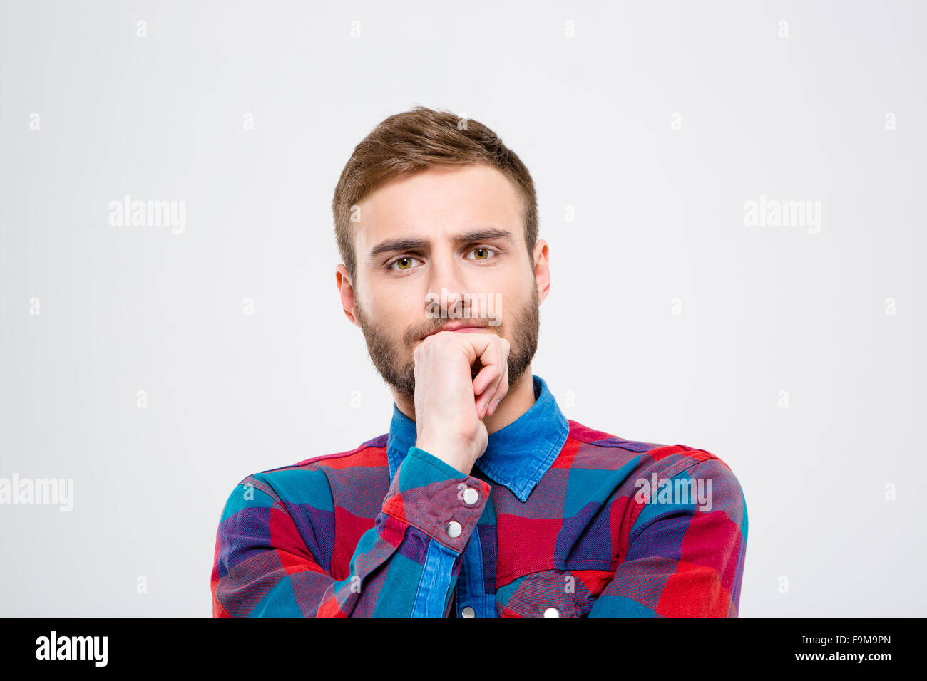Portrait of a pensive casual man looking at camera isolated on a white background - Stock Image