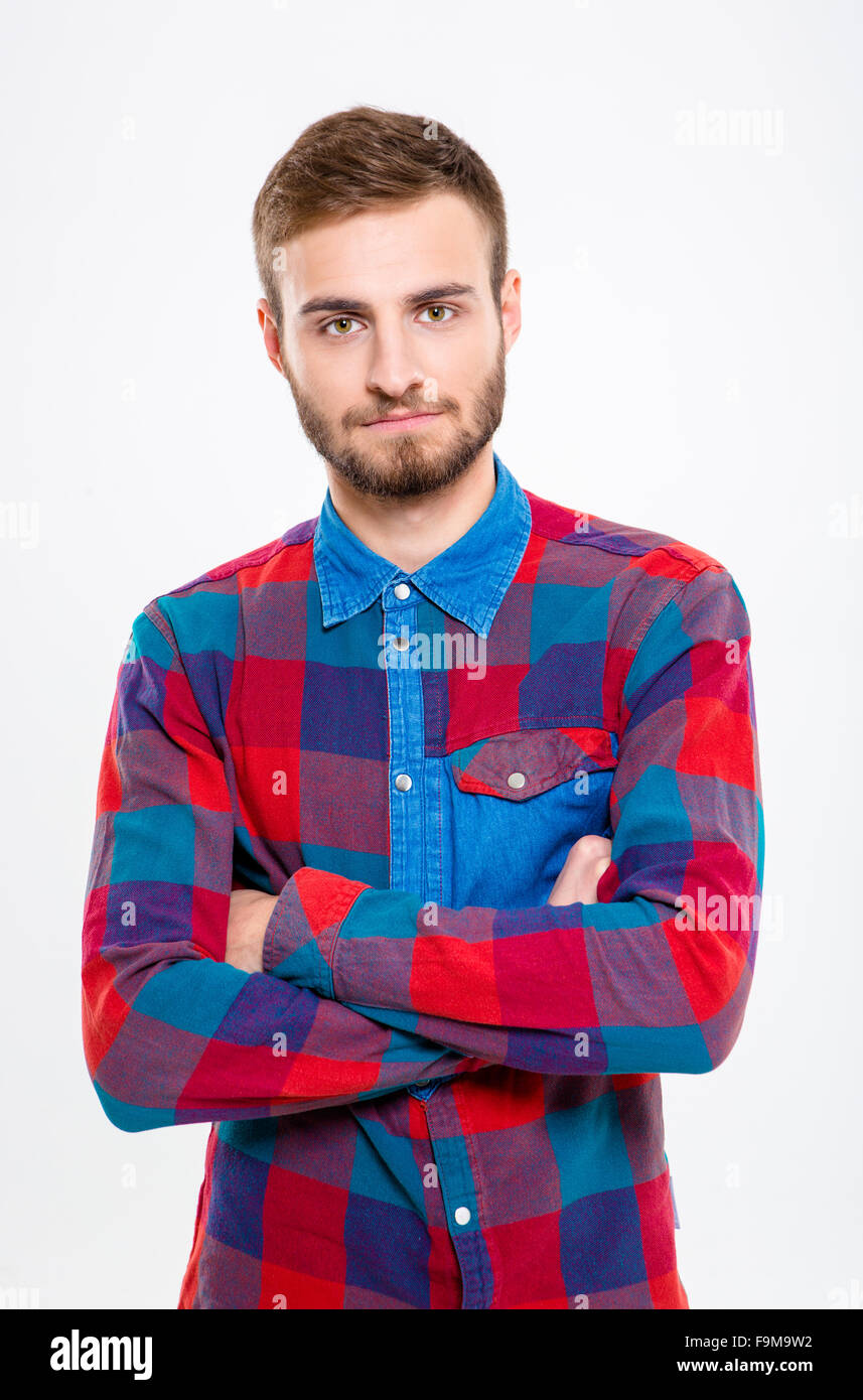 Portrait of a serious casual man standing with arms folded isolated on a white background - Stock Image