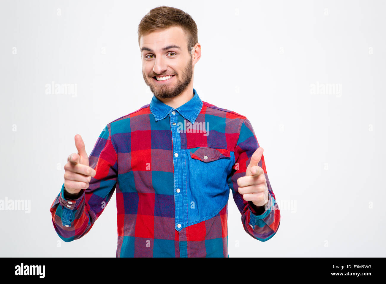 Portrait of a smiling man pointing finger at camera isolated on a white background - Stock Image