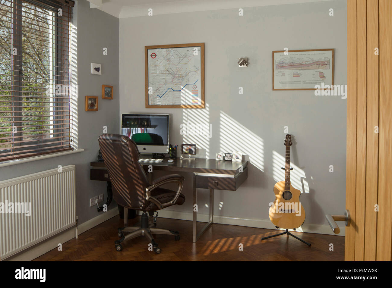 Home office study. A guitar, computer monitor and keyboard on a desk. White walls. - Stock Image