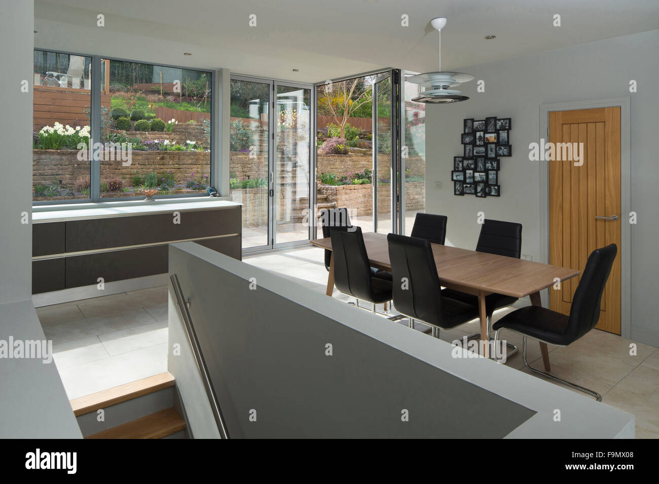A large open plan area, a kitchen and dining area, with views out of the large full size glass wall panels onto - Stock Image