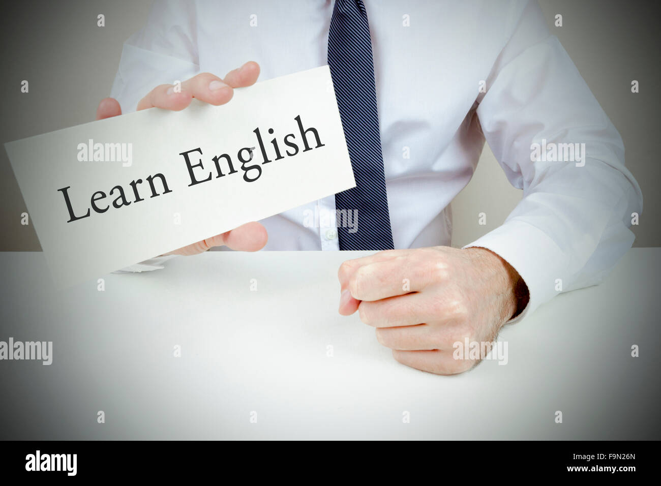A man dressed in shirt and tie holding up a card to learn English - Stock Image