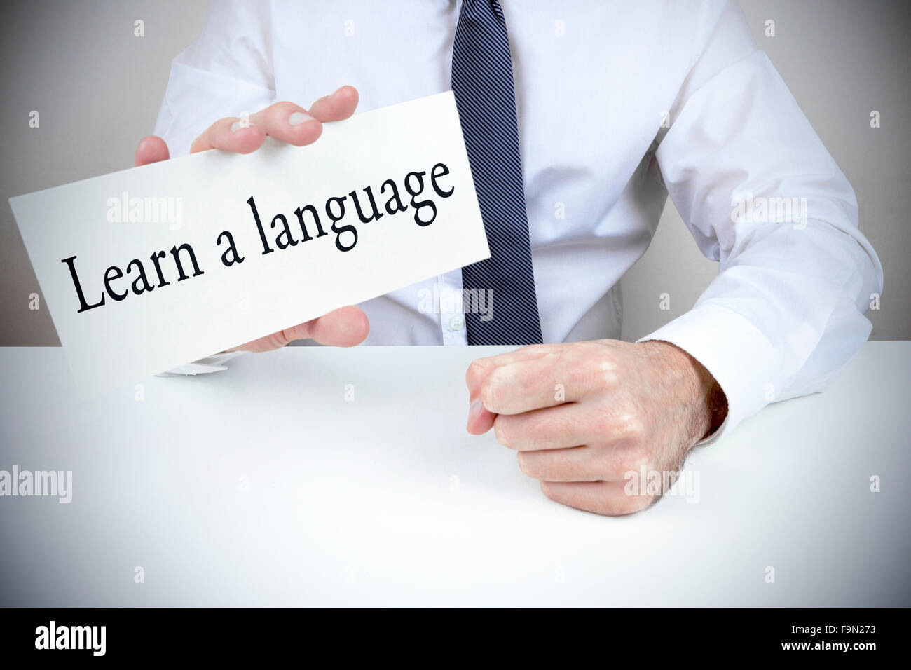 A man dressed in shirt and tie holding up a card to learn a language - Stock Image