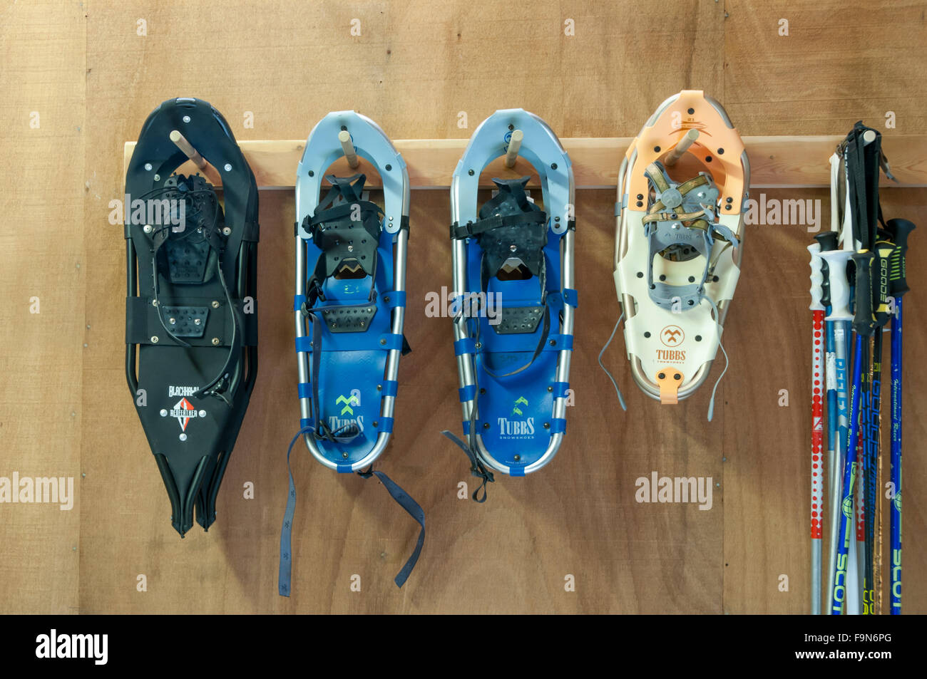 Pairs of snowshoes hanging up waiting for the winter snow and sports season. - Stock Image