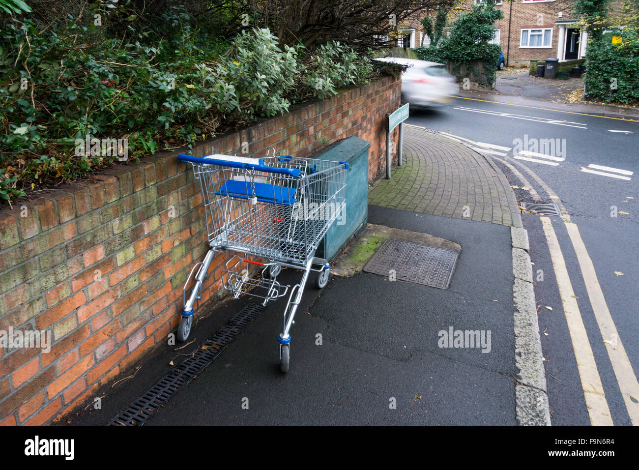 An abandoned supermarket trolley near a busy suburban road in south London. - Stock Image