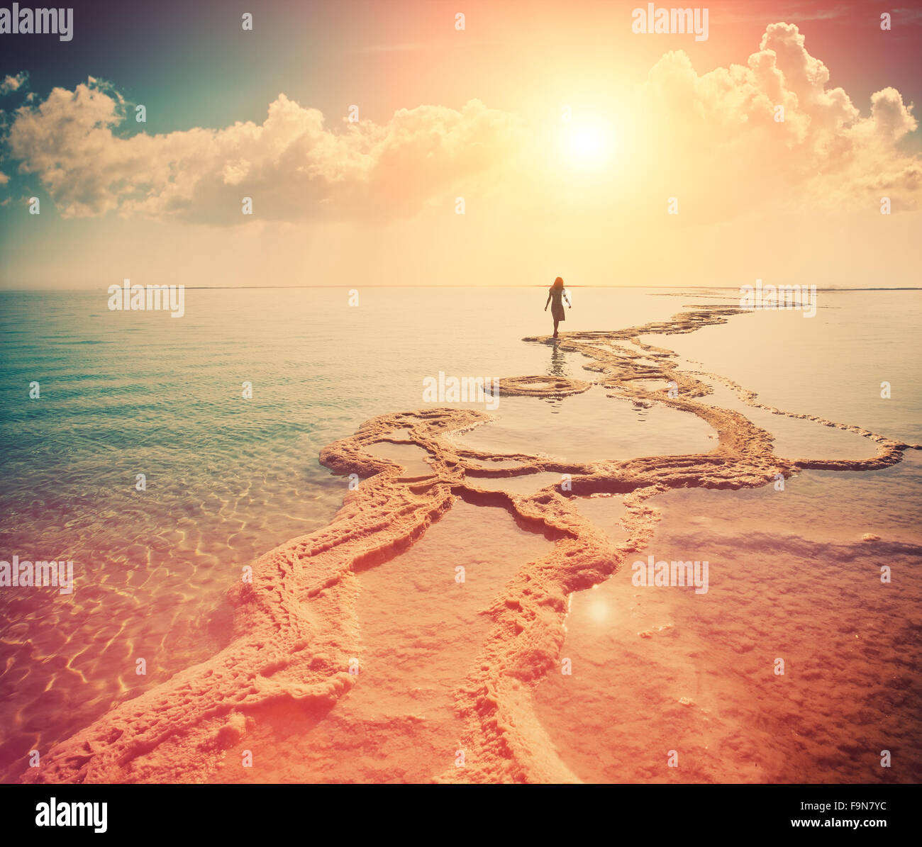 Silhouette of young woman walking on Dead Sea - Stock Image