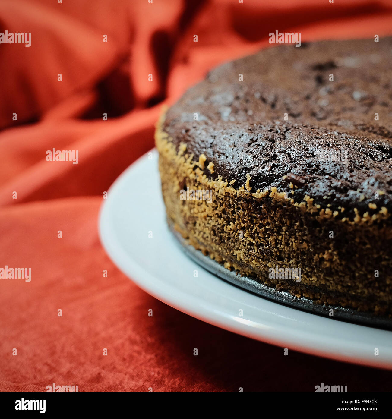 Dark Chocolate Mousse Cake Green & Blacks on white plate with red background - Stock Image