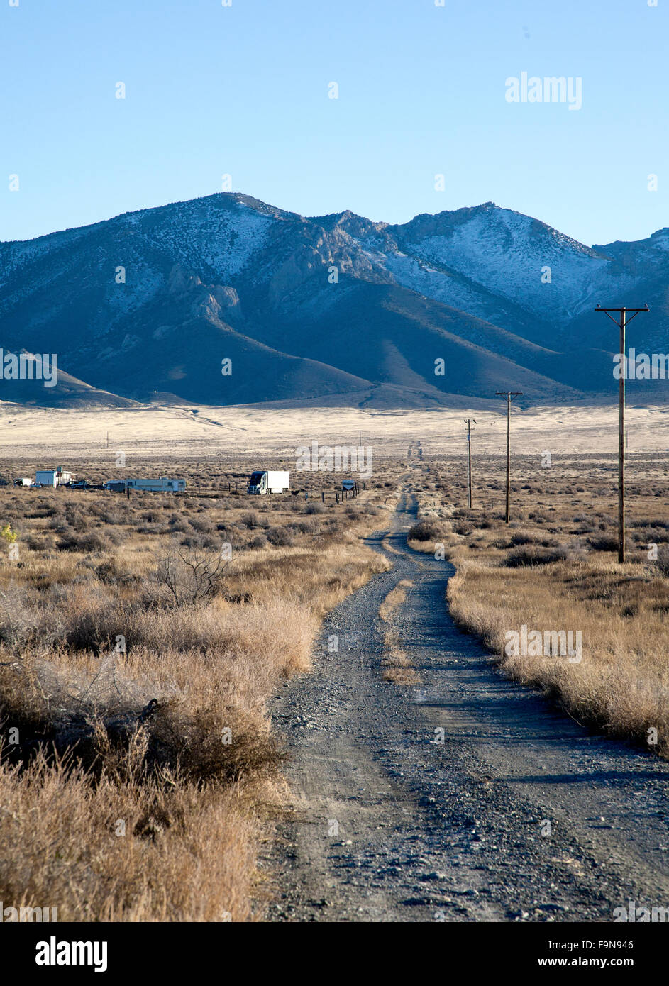 Gravel and dirt road leads to mountain with snow in the Nevada desert, US, 2015. - Stock Image