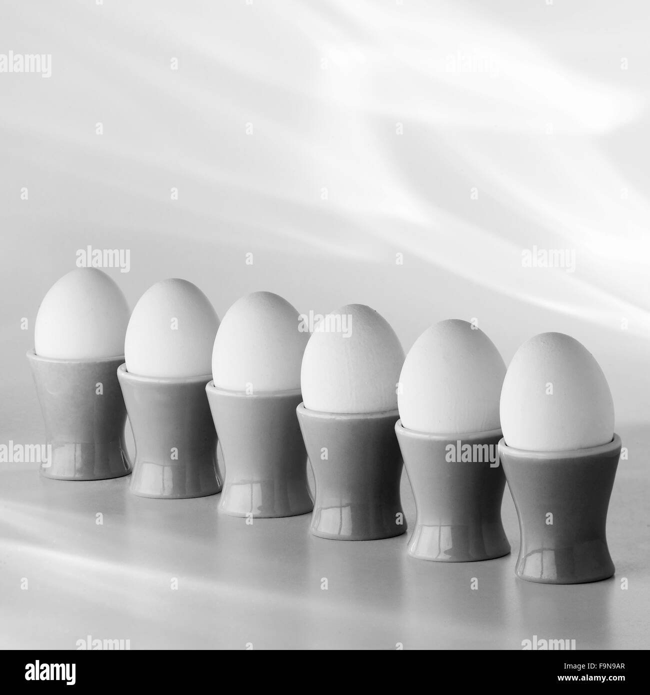 eggs in eggcups in a row - Stock Image