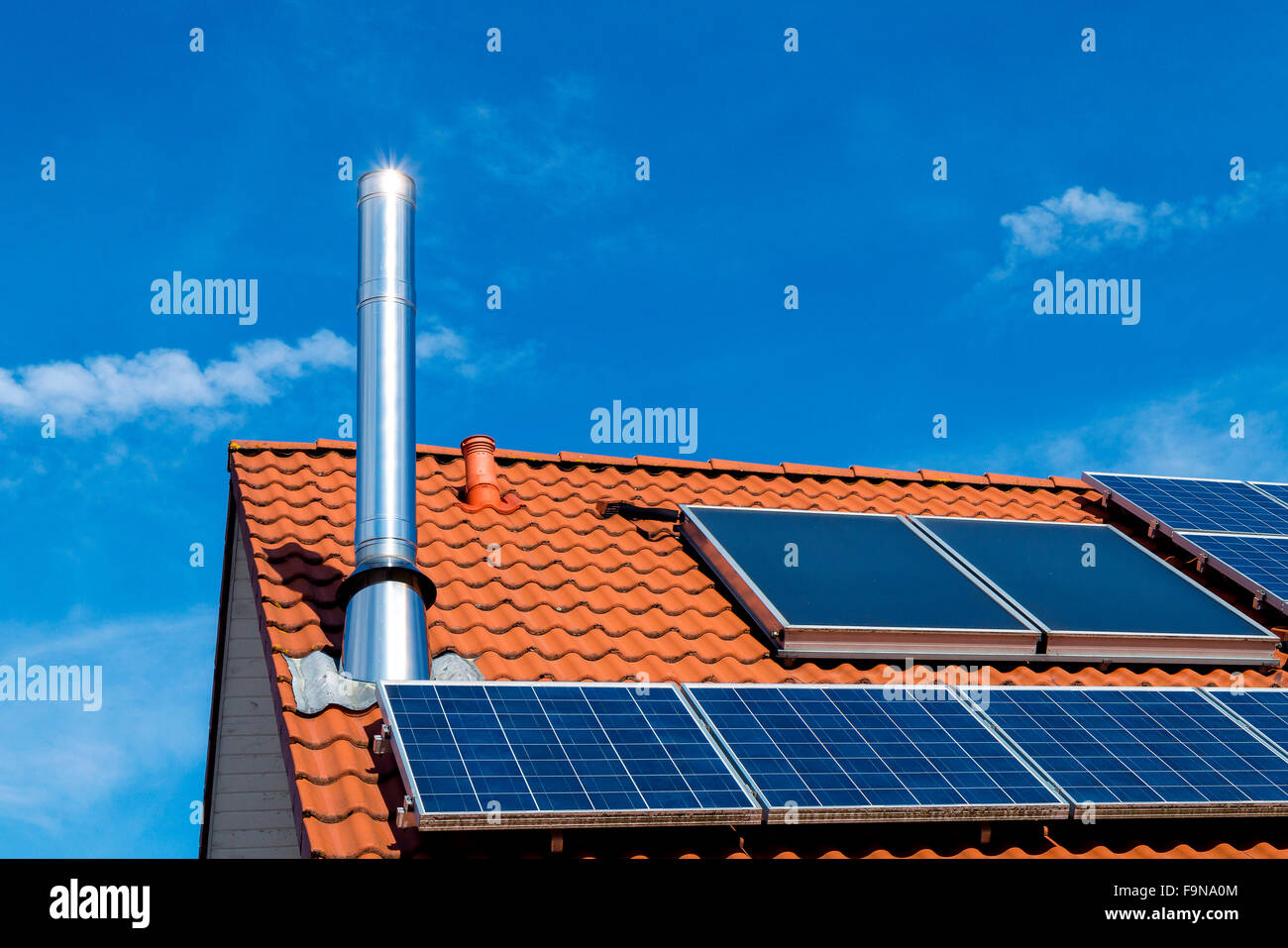 House roof with solar panels, stainless steel chimney, energy transition - Stock Image