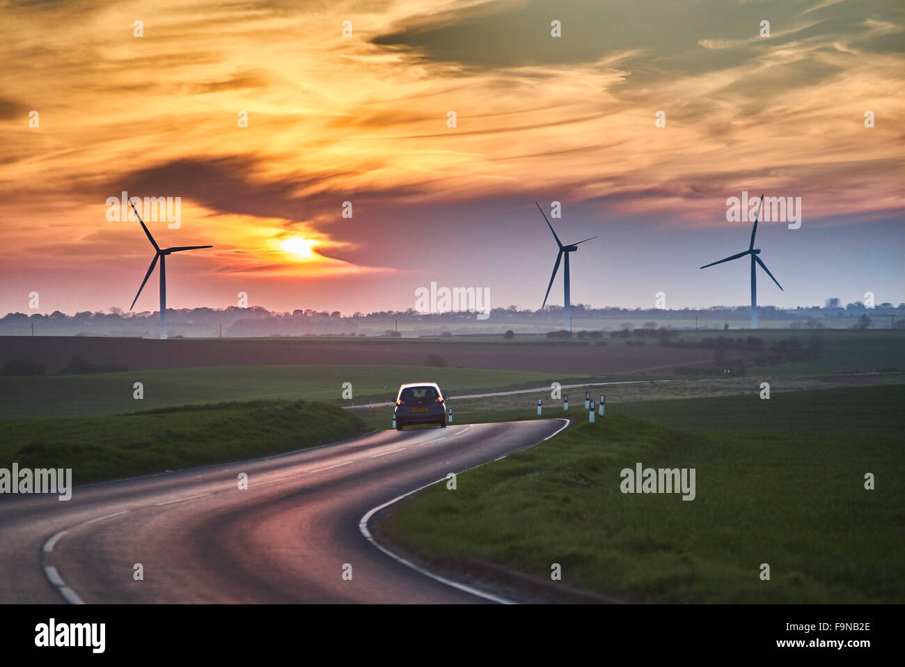 Wind turbines at a wind farm on farm land in Yorkshire during a summer sunset - Stock Image