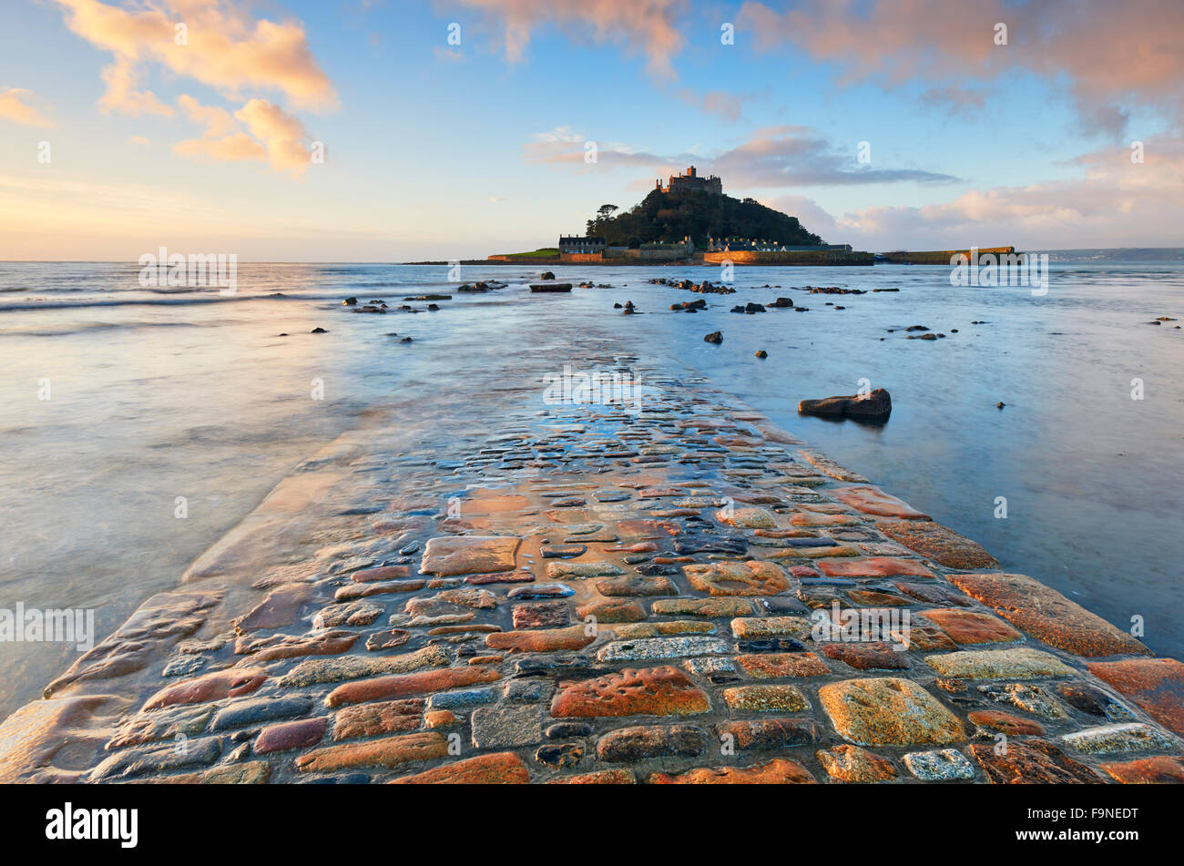 The receding tide reveals a view of the cobbled causeway that connects St Michael's Mount with the mainland - Stock Image