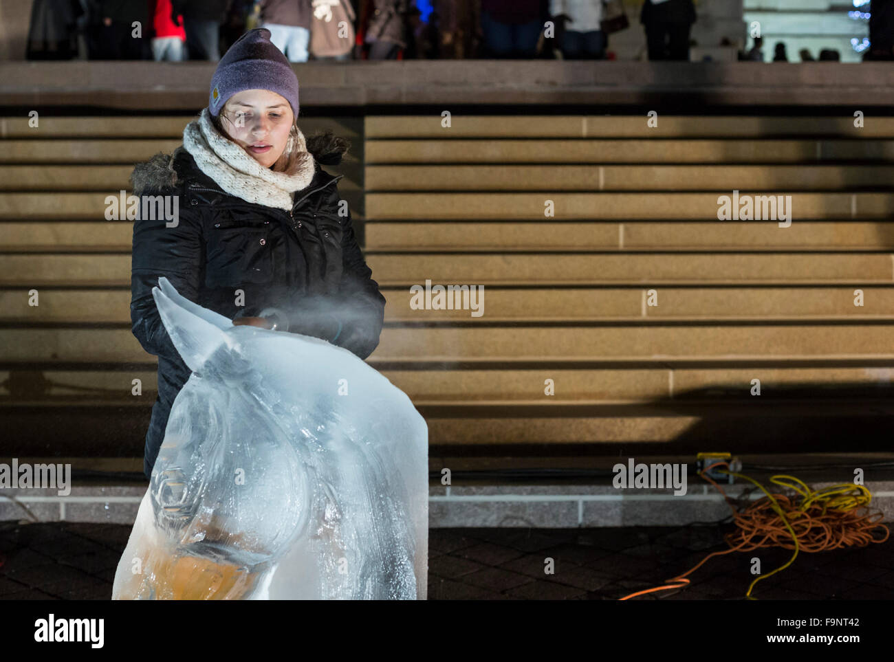 Detroit, Michigan - An artist makes an ice sculpture in front of the Detroit Institute of Arts during Noel Night. - Stock Image
