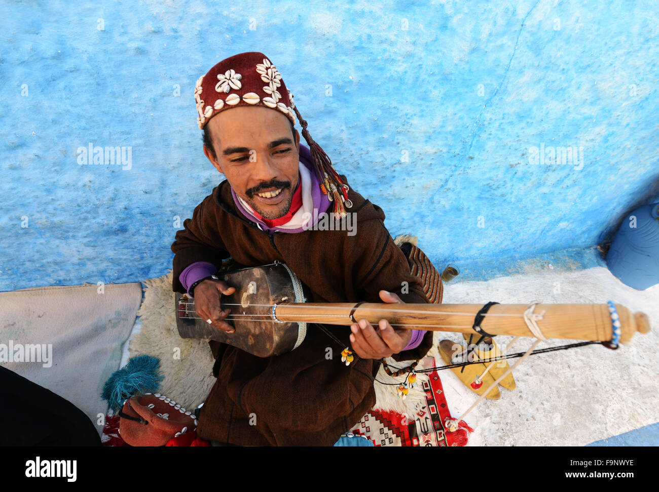 A Gnawa musician playing the Sintir in the kasbah or Rabat. - Stock Image