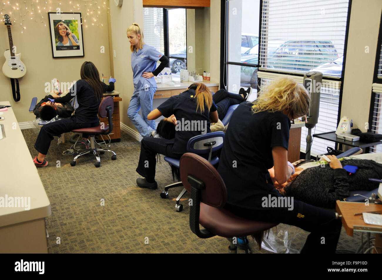 An orthodontist is a dentist who specializes in straightening crooked teeth.  Several assistants adjusting braces - Stock Image