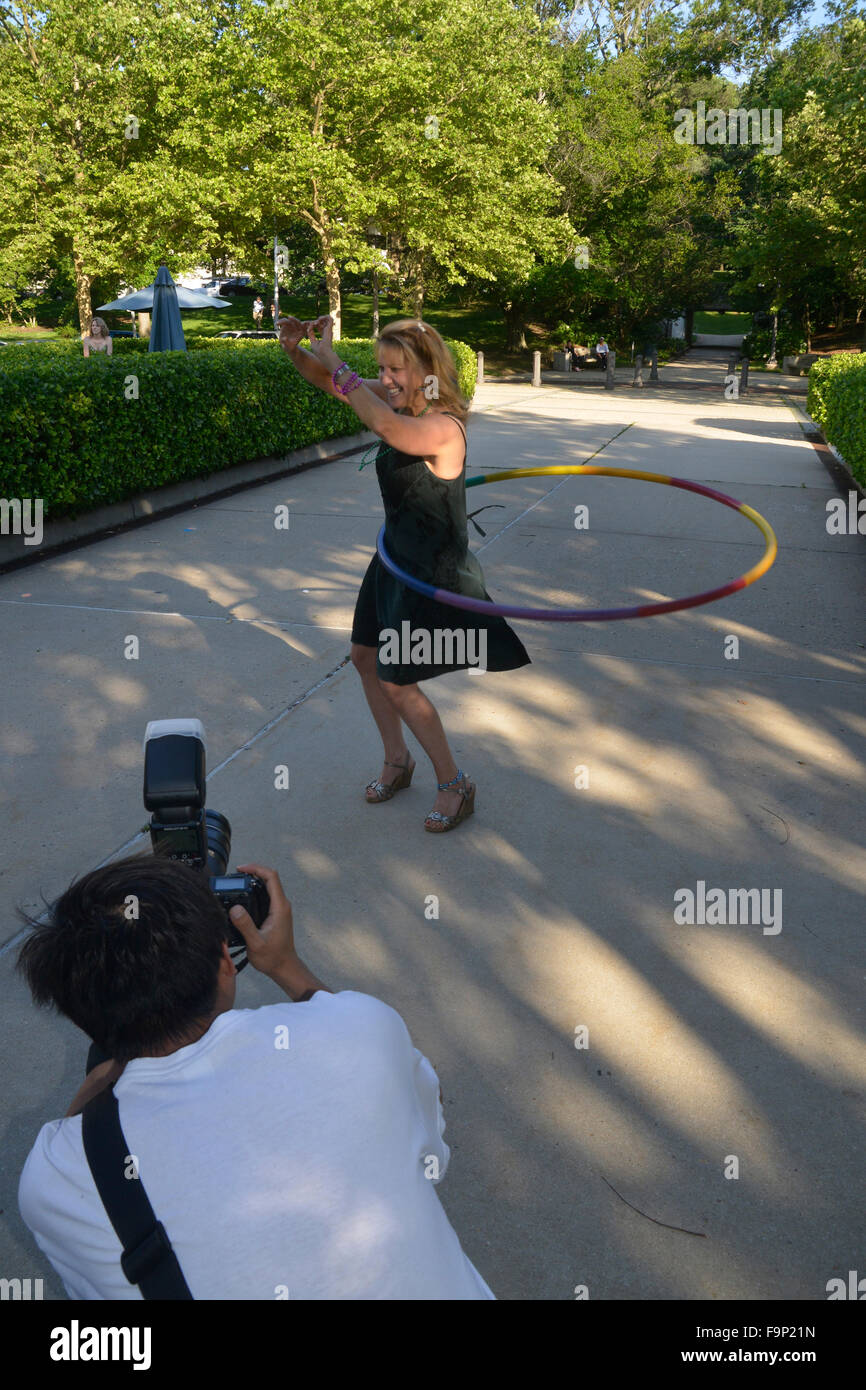 woman enjoys a hula hoop while a photographer takes pictures of her - Stock Image