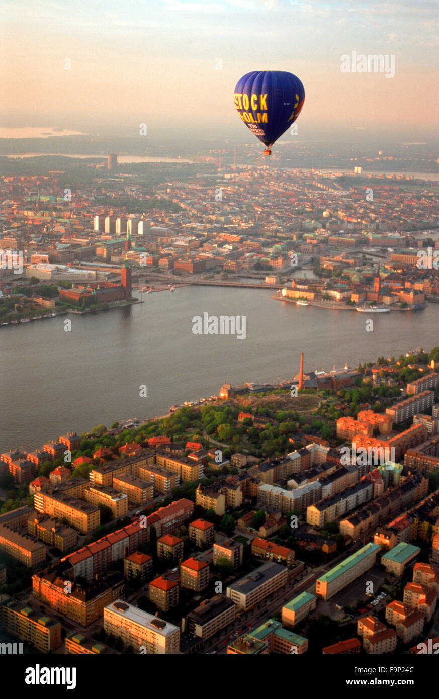 Hot air balloon floating over Södermalm and islands of Stockholm with City Hall on Riddarfjarden waters at sunset Stock Photo
