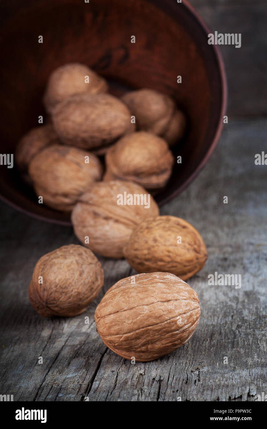 walnuts in clay bowl on wooden table - Stock Image