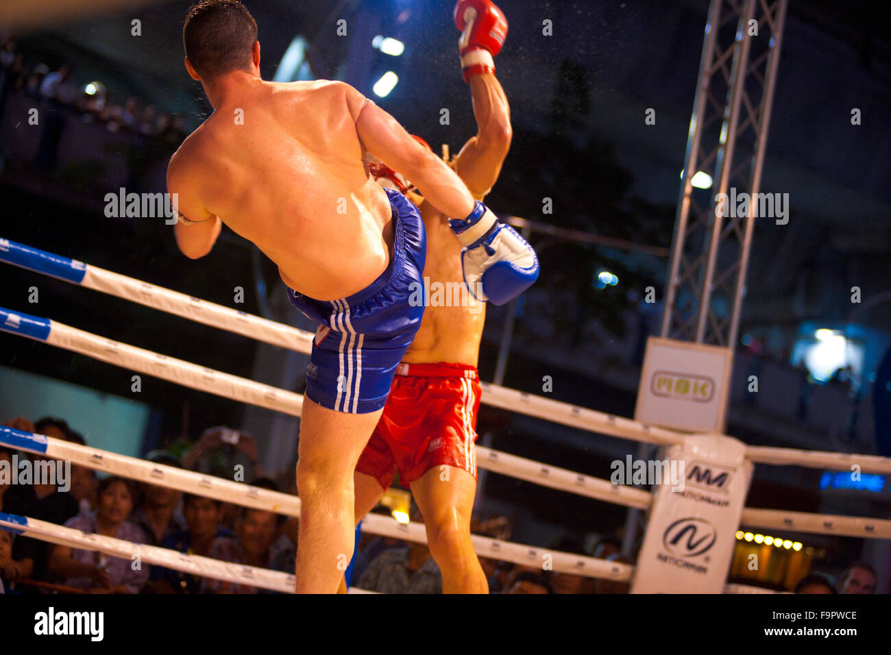 Male muay thai kickboxer kicking solid shot to opponent's head launching sweat flying everywhere at amateur - Stock Image