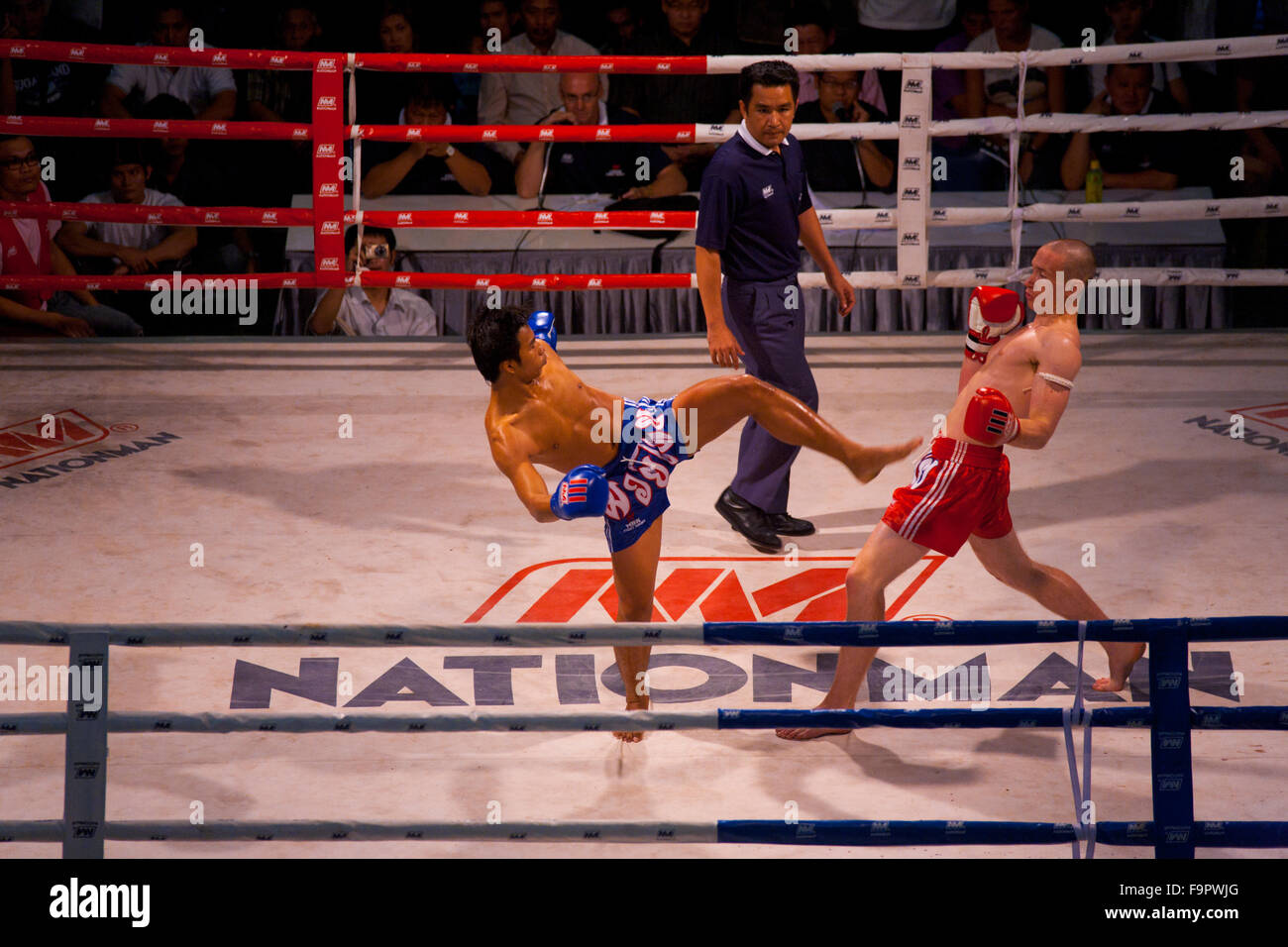 Caucasian man muay thai kickboxer dodging kick from Thai opponent at amateur night outdoor match - Stock Image