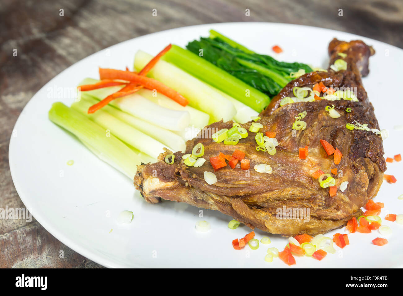 crispy duck drumstick, deep fried and eat with slice cucumber, flowering cabbage and onion spring, garnish on white - Stock Image
