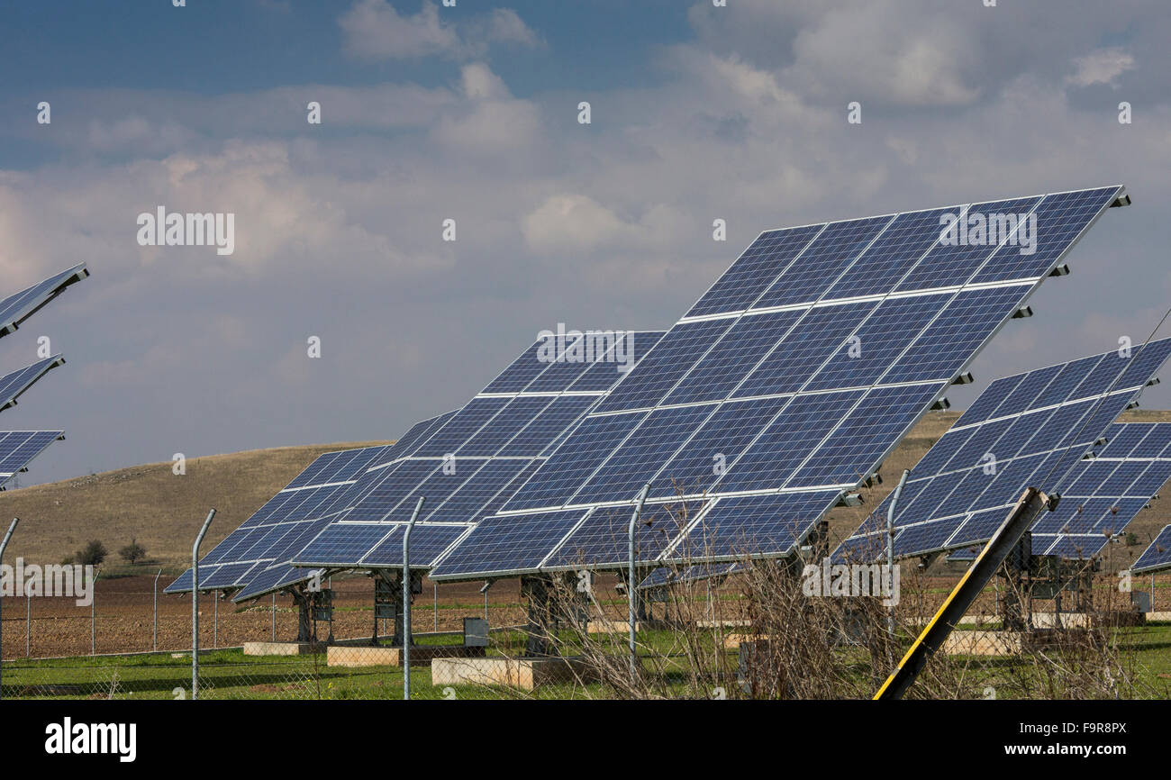 Solar panels and polluting coal-fired (lignite) power station beyond, Aghios Dimitrios, nr. Kozani, North Greece. - Stock Image