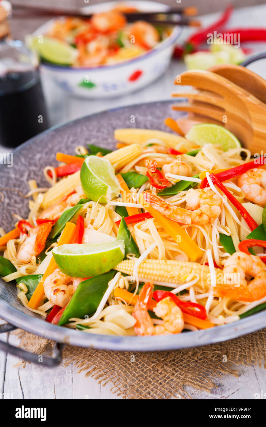 A healthy stir-fry of shrimp and vegetables served over noodles. - Stock Image