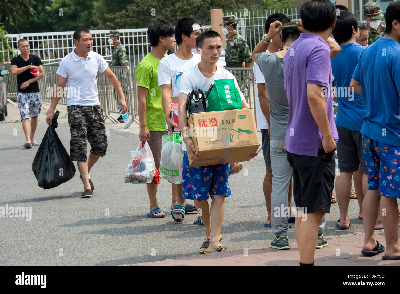 Tianjin Explosion aftermath People gather around the school camp to get there temporary ID cards as they are being - Stock Image