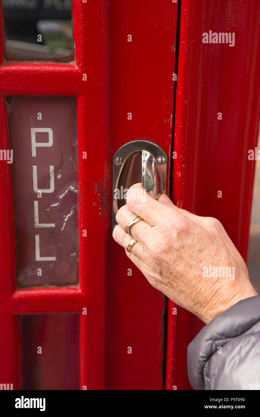 UK, England, Worcestershire, Bromsgrove, Avoncroft Museum, National Telephone Kiosk Collection, woman's hand opening - Stock Image