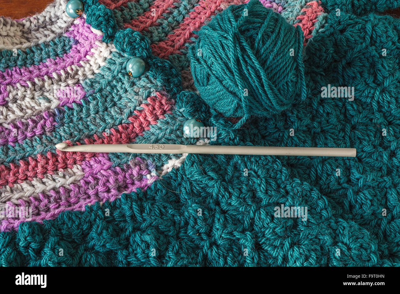 Crocheted baby sweater with a crochet hook and ball of yarn. - Stock Image
