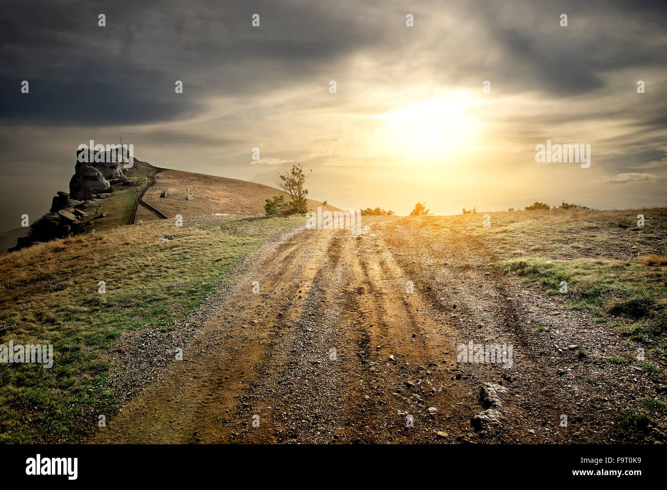 Stony road in mountains at the sunset - Stock Image