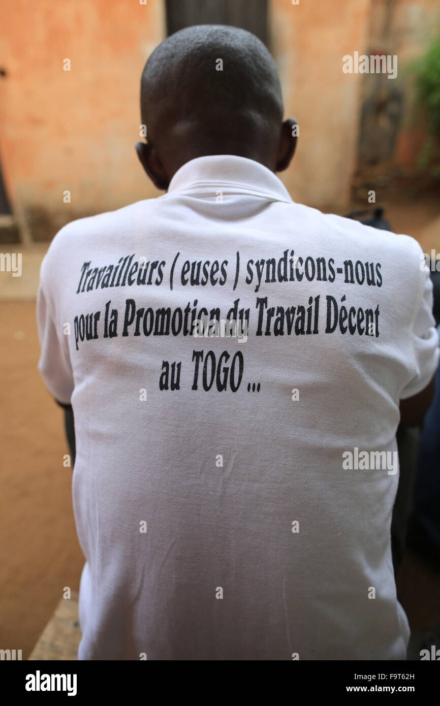 Slogan on a t-shirt: 'Workers (Artists) let's unite for Promoting Decent Work in Togo ...' - Stock Image