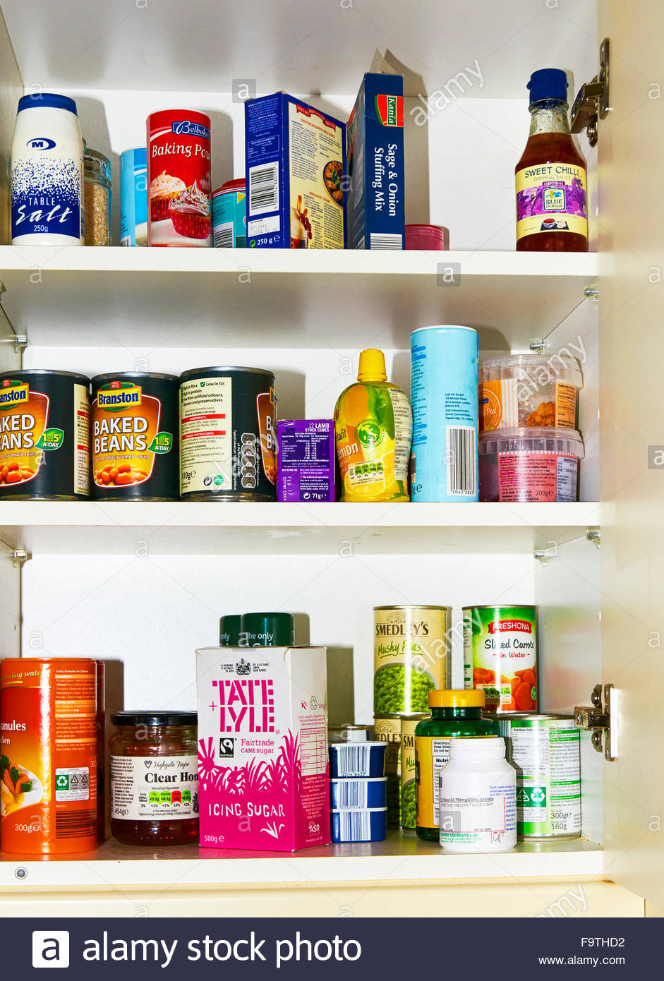 A well stocked food kitchen cupboard with packets and tins of various foodstuffs - Stock Image