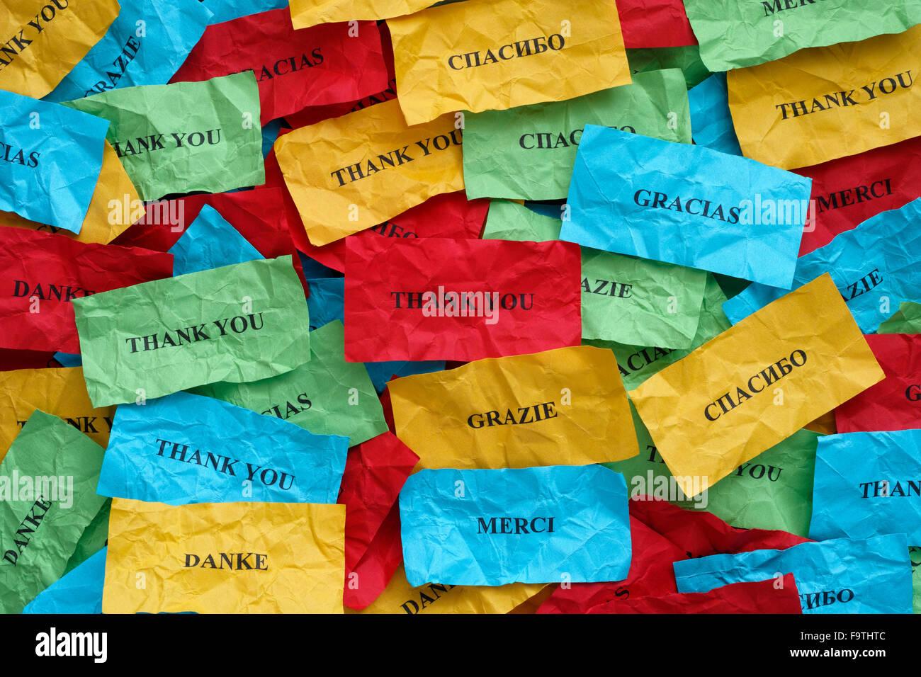 Thank you in many languages on crumpled colorful pieces of paper. - Stock Image