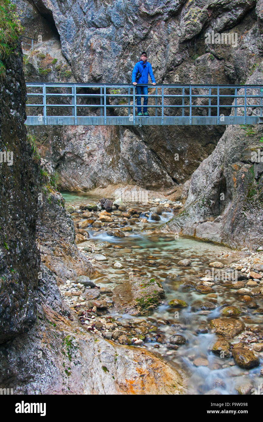 Tourist on footbridge over the river Almbach running through the Almbachklamm canyon in the Berchtesgaden Alps, - Stock Image