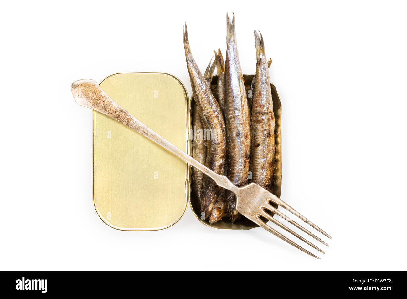 Open can with grilles anchovies isolated on white background, top view with lemon slice and fork isolated on white - Stock Image