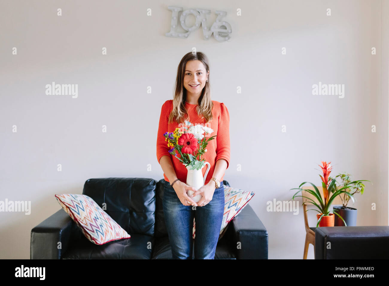 Portrait of smiling young woman with bunch of flowers in her living room - Stock Image