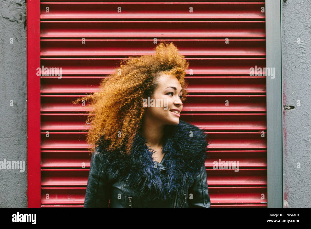 Ireland, Dublin, smiling woman with afro in front of red roller shutter - Stock Image